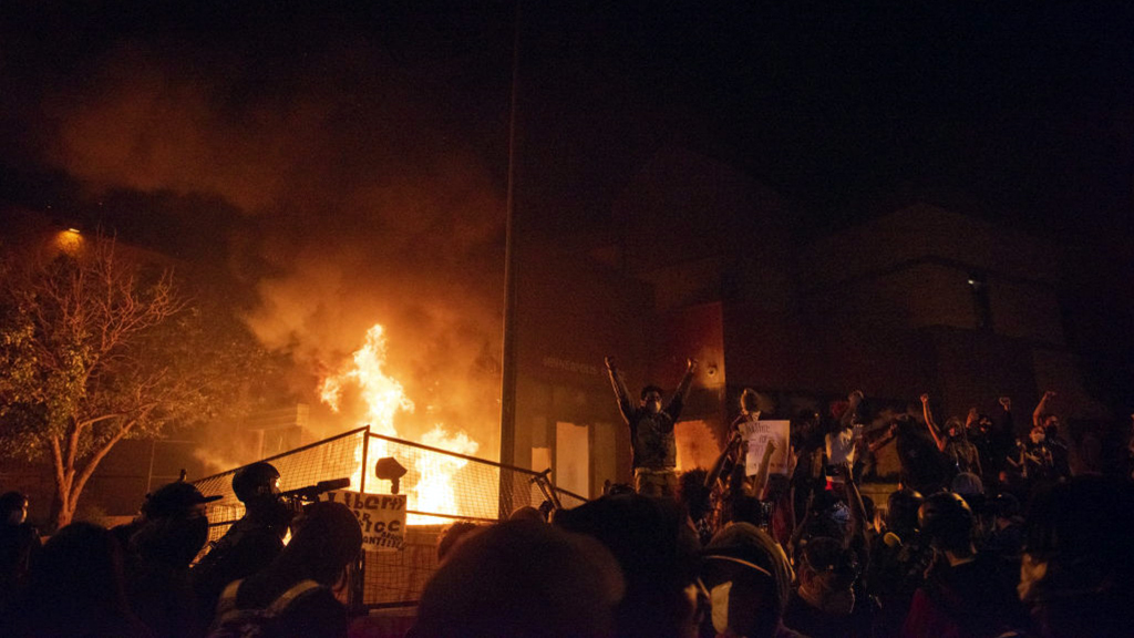 MINNESOTA, USA - MAY 28: Protestors stand on top of a broken fence while the Minneapolis Police 3rd precinct burns behind them on Thursday, March 28, 2020, during the third day of protests over the death of George Floyd in Minneapolis. Floyd died in police custody in Minneapolis on Monday night, after an officer held his knee into Floyd's neck for more than 8 minutes. (Photo by Steel Brooks/Anadolu Agency)