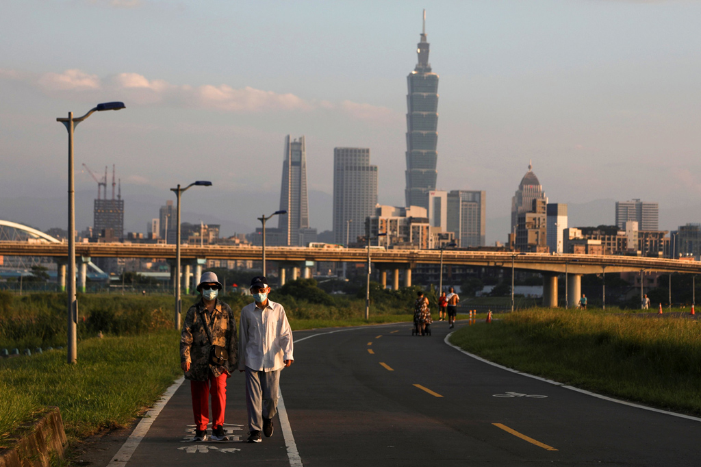 People wear protective masks to prevent the spread of the coronavirus as they walk on a river path at sunset in Taipei, Taiwan, Aug. 6, 2020. (Reuters Photo)