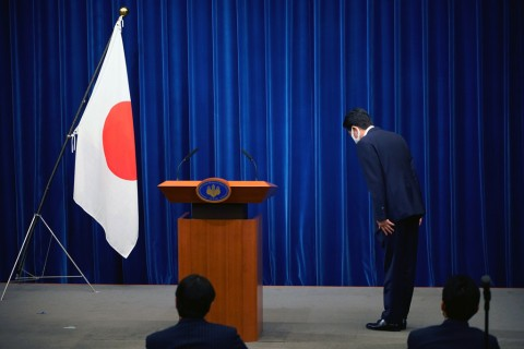 Japanese Prime Minister Shinzo Abe bows to the national flag at the start of a press conference at the prime minister official residence in Tokyo, Aug. 28, 2020. (AFP Photo)