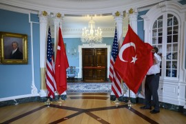 A U.S. State Department staffer adjusts a Turkish flag before a meeting between Foreign Minister Mevlüt Çavuşoğlu and U.S. Secretary of State Mike Pompeo, at the U.S. Department of State in Washington, D.C., April 3, 2019. (AFP Photo)