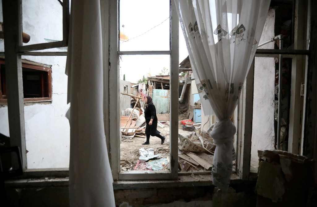 A woman walks past a house damaged by recent Armenian shelling in the city of Ganja, Azerbaijan, Oct. 6, 2020. (Reuters Photo)