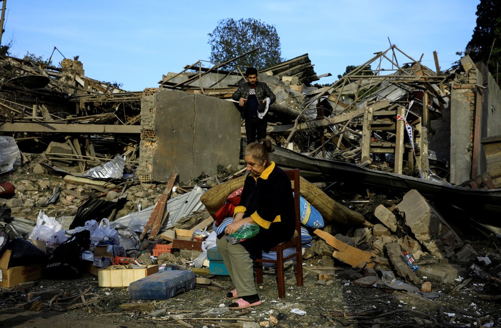 Vesile Mehmedova sits in front of the debris of her brother's home as her relatives search for belongings, at a blast site hit by an Armenian rocket in the city of Ganja, Azerbaijan, Oct. 11, 2020. (Reuters Photo)