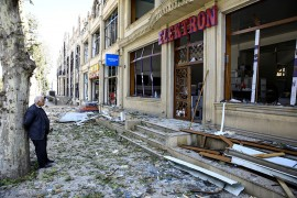 A shop owner stands in front of his store at a blast site from an Armenian rocket in the city of Ganja, Azerbaijan, Oct. 11, 2020. (Reuters Photo)