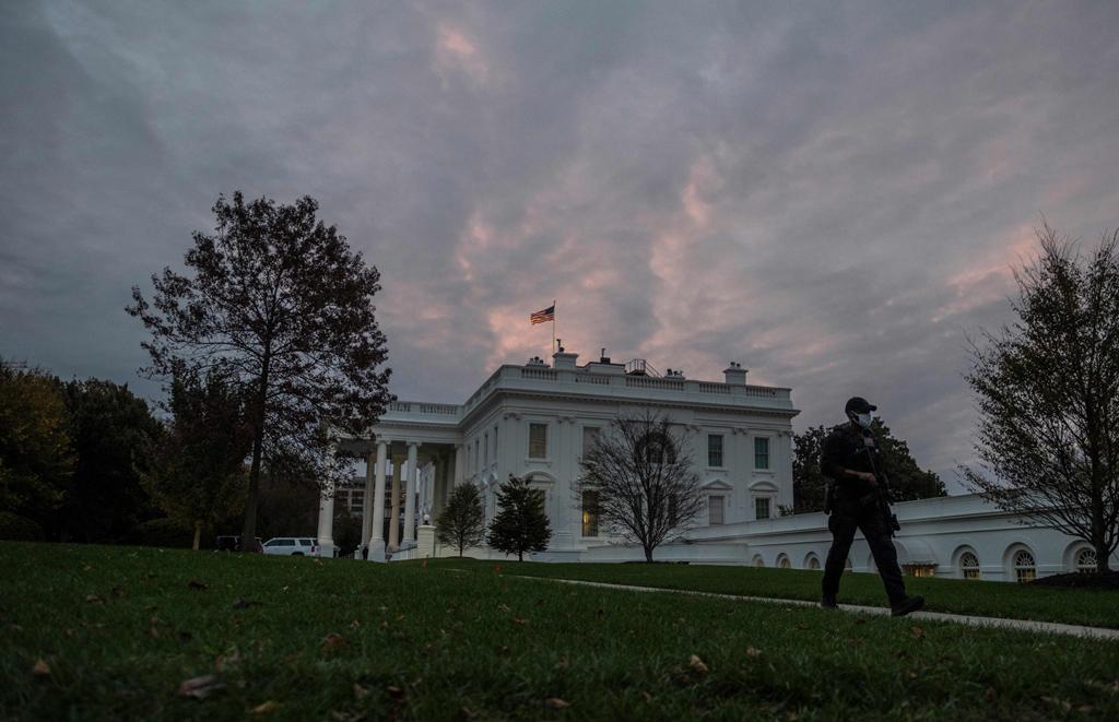 A U.S. agent walks down a path as the sun rises over the White House in Washington, D.C., Nov. 1, 2020. (AFP Photo)
